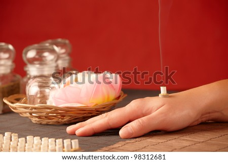 TCM Traditional Chinese Medicine. Smoking mini moxa stick on human hand, natural herbs in glass jars in background - stock photo