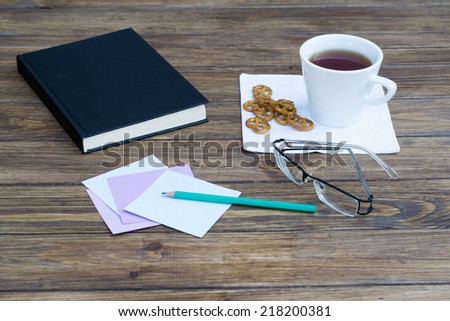tea and a book, paper and pencil on wooden table - stock photo