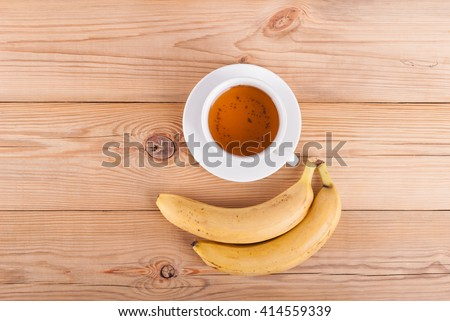 Tea and bananas on a wooden table. View from above .