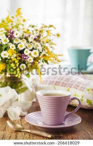 Tea and beautiful wildflowers on wooden background - stock photo