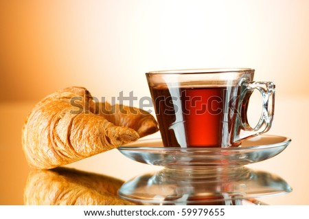 Tea and croissants on the reflective background
