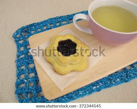 Tea and flower biscuit filled with blueberry jam - stock photo