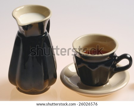 Tea and milk in black cups isolated on a white background - stock photo