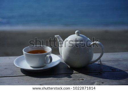 https://thumb7.shutterstock.com/display_pic_with_logo/167494286/1022871814/stock-photo-tea-and-sea-by-seaside-cafe-1022871814.jpg
