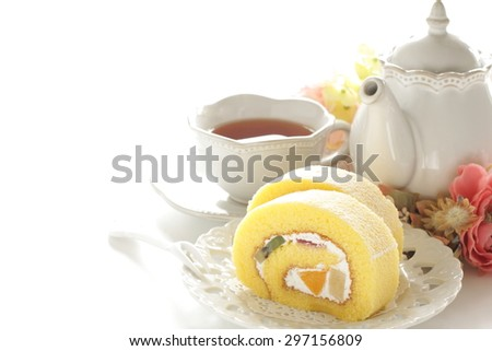 tea and swiss roll with flower - stock photo