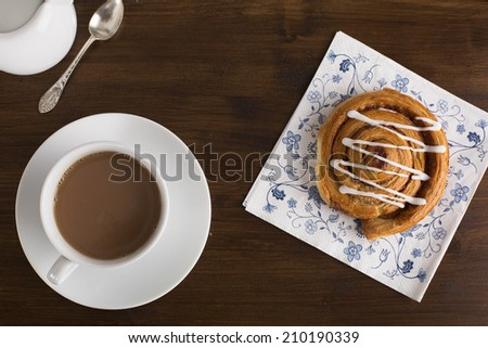 Tea and tempting cinnamon roll from above. - stock photo