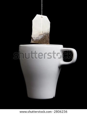 Tea bag being pulled out of a white teacup after steeping. - stock photo