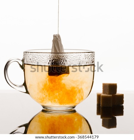 Tea bag brewing in the cup on the glass table with white background