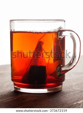 Tea bag in glass mug on wooden table close-up macro shot, vertical - stock photo