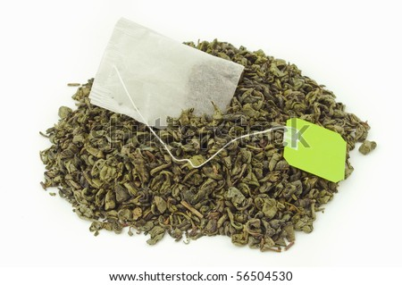 Tea bag inside a mount of dried green tea leaves - stock photo