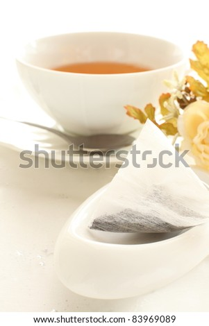Tea bag on white background with flower and tea