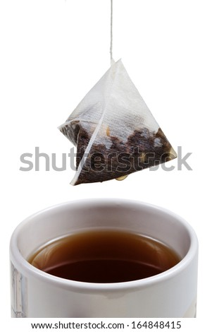 tea bag over brewing tea in cup close up isolated on white background - stock photo