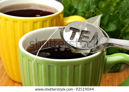 Tea bag squeezer with tea bag and colorful mugs filled with freshly brewed hot tea.  Lemon balm herb plant in soft focus in background.  Macro with shallow dof.  Selective focus on the word - TEA. - stock photo