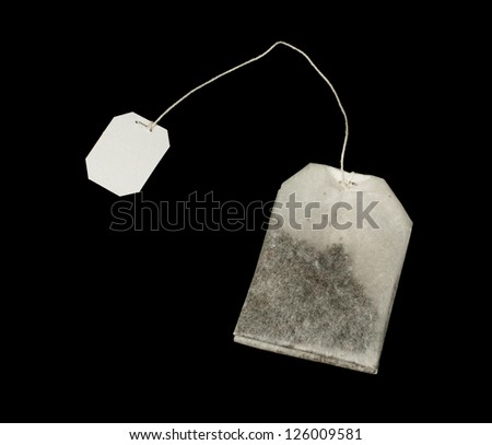 Tea bag with white label close up black isolated