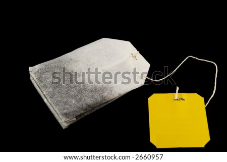 tea bag with yellow label isolated on black