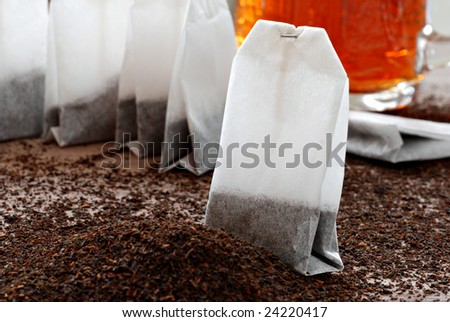 Tea bags and dried tea leaves with  prepared tea in the background.   Macro still life with shallow dof. - stock photo