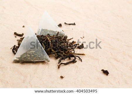 tea bags and loose green tea on a wooden background  - stock photo