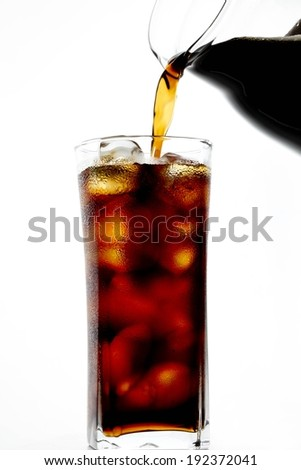 Tea being poured from a pitcher into a tall glass. - stock photo