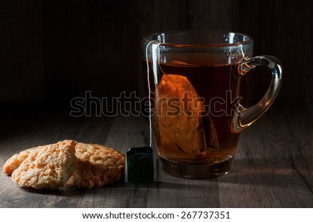 Tea, black, classic, a glass mug. With mugs hanging tea bag. Next to a cup of two pieces of biscuits