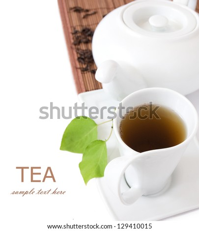 Tea breakfast (cup of tea, fresh green leaves, tea pot and bamboo mat isolated on white background with sample text) - stock photo