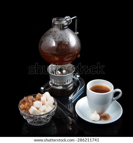 tea burner welding sugar cup vessel cane sugar background black - stock photo