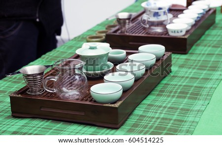 Tea ceremony.Hot tea will be poured into cups for tasting. Tray made of mahogany with six cups, tea maker, teapot,  glass jug for hot water is on the table