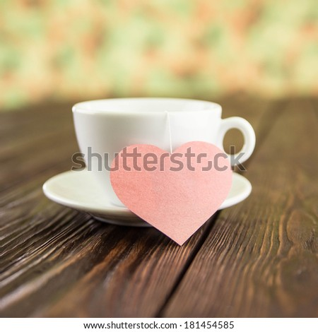 tea ceremony with heart on an old wooden background - stock photo