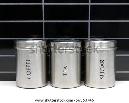 Tea coffee and sugar canisters on a kitchen bench - stock photo