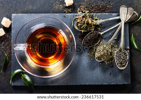 Tea composition with old spoon on dark background - stock photo