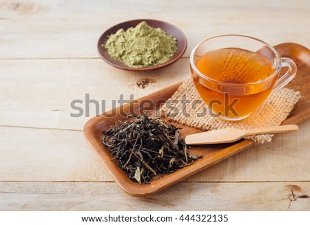 tea cup and dried tea leaves with green tea powder on wooden background