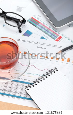 Tea cup and empty notepad on contemporary workplace with financial papers, office supplies and tablet