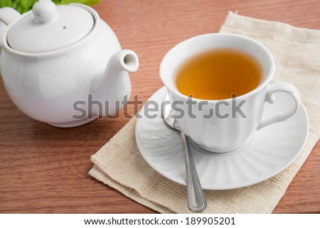 tea cup and tea pot on table - stock photo