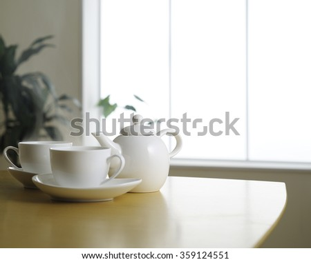 tea cup and tea pot on wooden table - stock photo