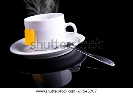 Tea cup and tea spoon on black background - stock photo