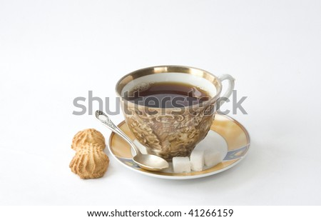 Tea cup on saucer with sugar and baking