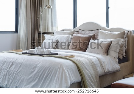 tea cup set on classic bed with pillows at home - stock photo