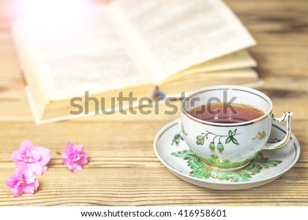 Tea cup, the book and flowers on the wooden table. Image with light effects, toning. Shallow DOF - stock photo