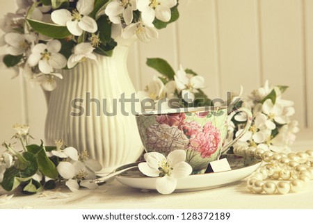 Tea cup with fresh apple blossoms on table - stock photo