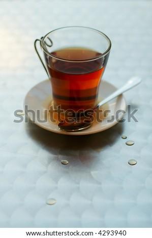 Tea cup with hot spilt tea - stock photo