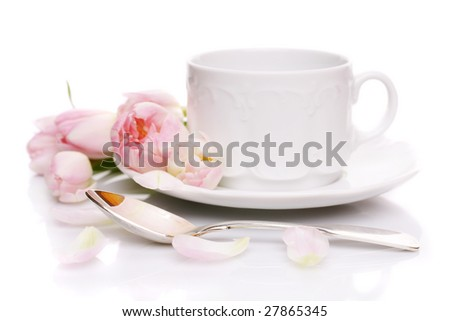 Tea cup with pink tulips on white background - stock photo