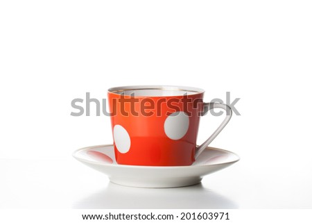 Tea cup  with saucer, red color with white dots, on white background. Tea set. Tea time. Coffee time. Porcelain dishes - stock photo