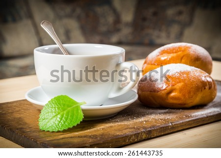 Tea cup with two buns on wooden table - stock photo