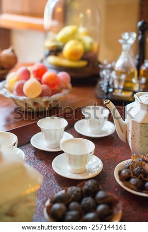 Tea, cups and sweets on the table. - stock photo