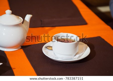 Tea cups and teapot standing on the table in cafe decorated in black and orange colors