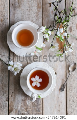 tea cups on wooden table with almond blossom - stock photo