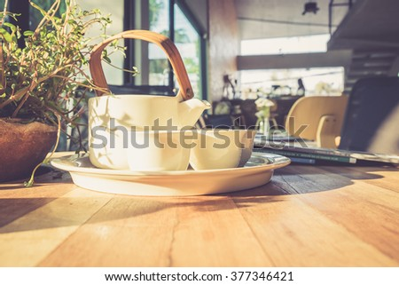 tea cups set on wooden table in coffee shop with vintage filter - stock photo