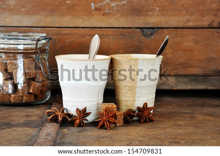 Tea cups with aniseed and brown sugar on old wooden table. - stock photo