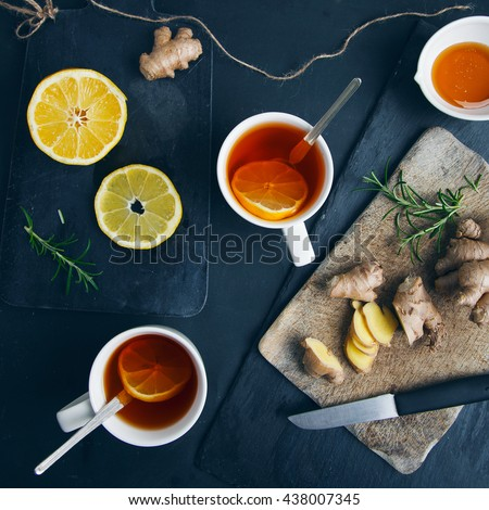 Tea cups with black tea, lemon, ginger - stock photo