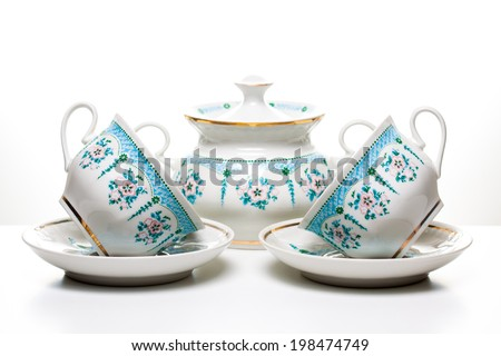 Tea cups with saucers and sugar bowl  on white background. Porcelain dishes, tableware. Ornamental tea set. Beautiful kitchenware. Decorative background. Tea time  - stock photo