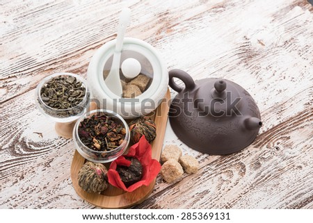 Tea cups with teapot on old wooden table - stock photo